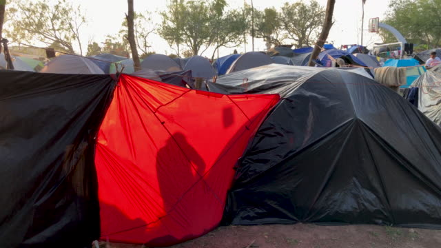 an immigrant from honduras cleans up her family's living area at a camp for asylum seekers on december 08, 2019 in the border town of matamoros,... - mexican american stock videos & royalty-free footage