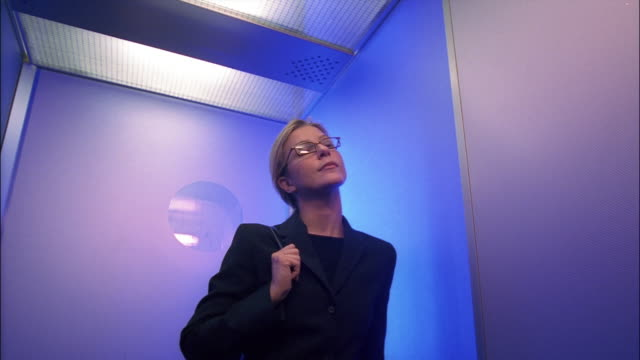 An impatient businesswoman checks her watch as she rides the elevator.