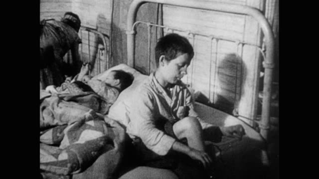 vidéos et rushes de an impovershed family lives together in crowded quarters - 1930