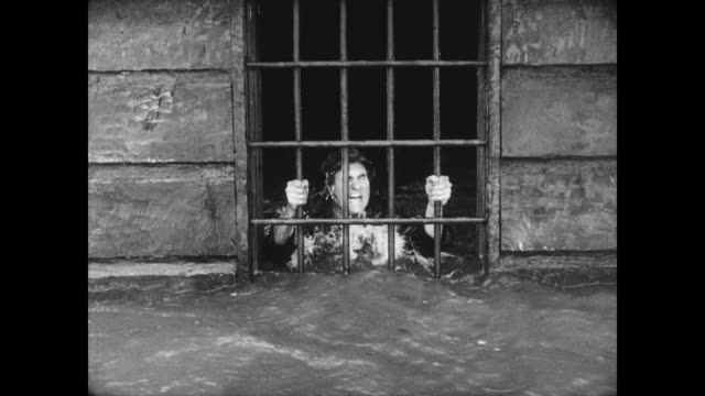 1928 an imprisoned man (ernest torrence) finds himself in danger of drowning when the jail is blown into the river - crash stock videos and b-roll footage