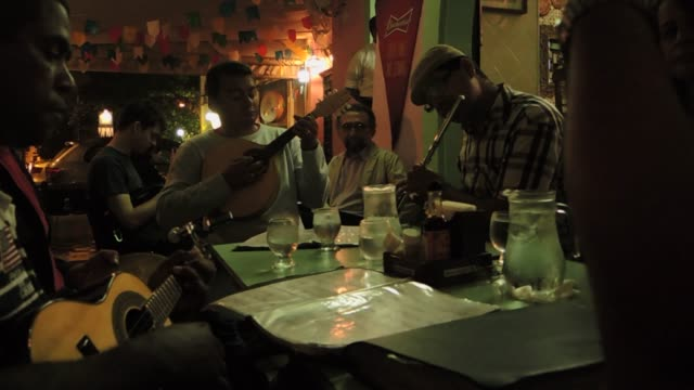 an improvised group of musicians play a beautiful brazilian tune after dinner - south america stock videos & royalty-free footage