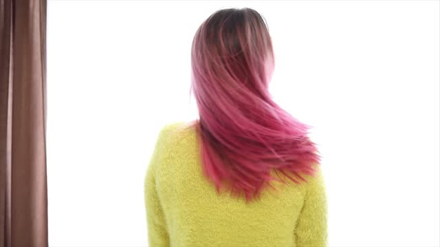 an independent young woman with pink hair poses by the window. slow motion - pink hair stock videos & royalty-free footage