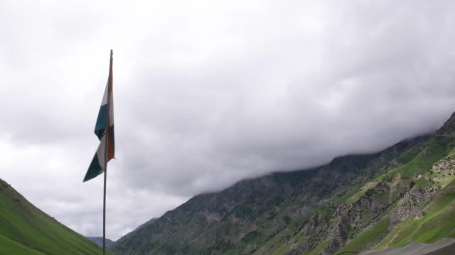 an indian army jawan passes in front of the indian national flag fluttering at a high altitude army post in upper kashmir himalayas along with the border with pakistan - army soldier stock videos & royalty-free footage