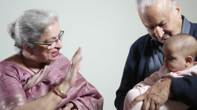 An Indian grandmother bids farewell to her granddaughter who is being held by her grandfather