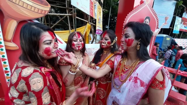 an indian hindu devotee smiles as she is smeared with vermillion powder as part of a ritual of 'sindhoor khela' on the occasion of the dushheravijaya... - dashahara stock-videos und b-roll-filmmaterial