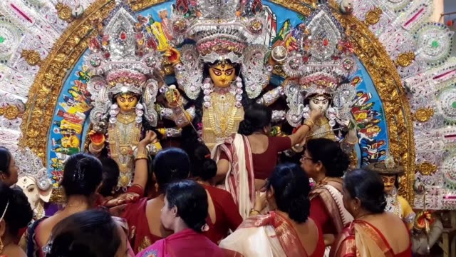 an indian hindu devotee worships an idol of the goddess durga as part of a ritual on the last day of vijaya dashami celebrated during durga puja... - dashahara stock-videos und b-roll-filmmaterial
