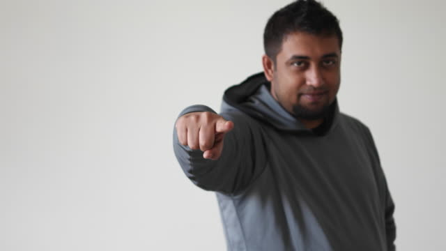 An Indian man pointing his finger towards the camera