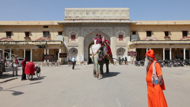 An Indian man rides a ceremonial decorated elephant outside the Palace of the Winds in Jaipur, India.
