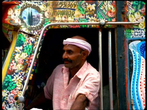 an indian man wearing a headband looks out from a decorated window. - hair band stock videos & royalty-free footage