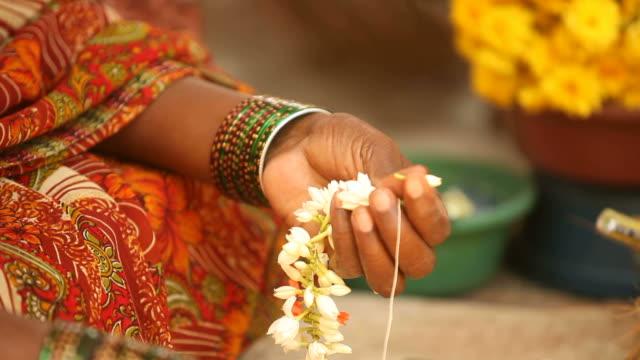 stockvideo's en b-roll-footage met an indian woman makes a garland of beautiful jasmine flowers - guirlande