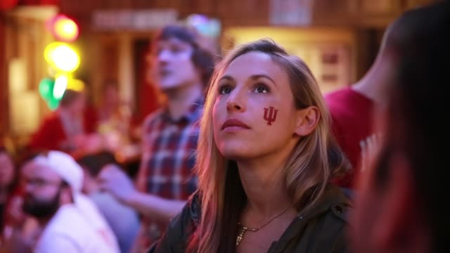 vídeos de stock, filmes e b-roll de an indiana university fan with the iu logo painted on her cheek cheers for the indiana university hoosiers who are playing against against kentucky... - bloomington indiana