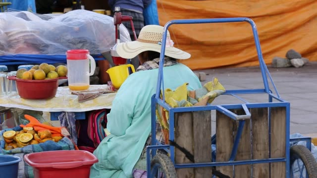an indigenous woman selling freshly squeezed orange juice at a street market in el alto la paz bolivia south america - orangensaft stock-videos und b-roll-filmmaterial