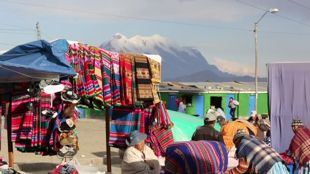 an indigenous woman selling traditional colourful bolivian fabric at a street market in el alto, la paz, bolivia. - south america stock videos & royalty-free footage