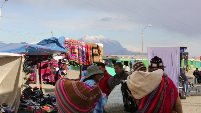 an indigenous woman selling traditional colourful bolivian fabric at a street market in el alto, la paz, bolivia. - ボリビア点の映像素材/bロール