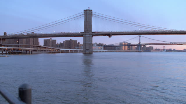 an indigo sky glows above the brooklyn bridge in new york city. - ponte video stock e b–roll