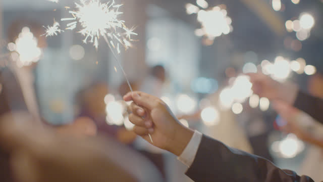 slo mo cu an individual holds a sparkler as a newlywed couple are sent off - dinner jacket stock videos & royalty-free footage