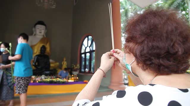 an indonesian buddhist pray as they hold an incense during vesak day at indonesia theravada buddhist centre on may 26 in medan, indonesia. buddhists... - albert damanik stock videos & royalty-free footage