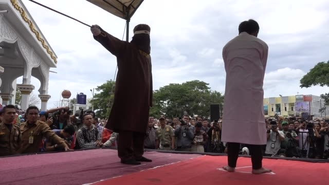 An Indonesian man gets caning in public from an executor known as 'algojo' for having gay sex which is against Sharia law on May 23 2017 in Banda...