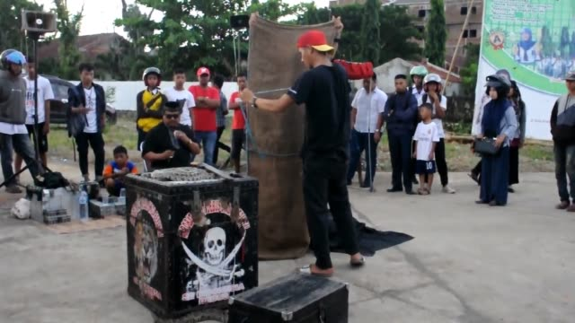 an indonesian street magician group performs at the main street of makassar city indonesia they brought a python snake to attract the commuters to... - 手品師点の映像素材/bロール