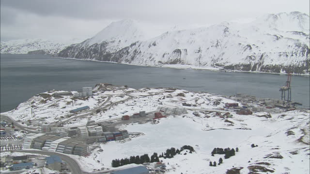 An industrial port lines Dutch Harbor and snowy mountains.