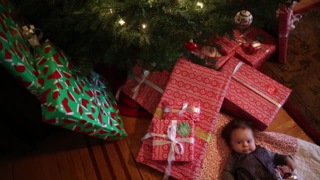 an infant girl lying underneath a christmas tree with presents around her - lying on back stock videos & royalty-free footage