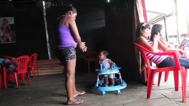 ls an infant sits inside a baby walker in a local village brothel the region of madre de dios in southeastern peru has been devastated by illegal... - bordell stock-videos und b-roll-filmmaterial