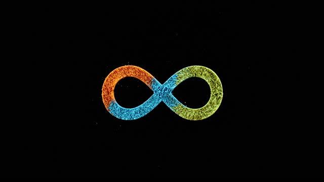 vídeos de stock, filmes e b-roll de slo mo ld um símbolo infinito emergindo quando poeira laranja, azul e amarela caem na superfície - infinito