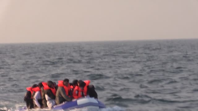vídeos de stock e filmes b-roll de an inflatable dinghy carrying around twenty syrian migrants has been met by border force off the coast of dover. the packed vessel had been making... - refugiado