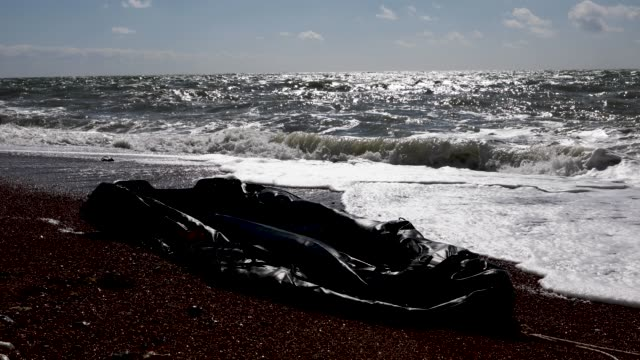 an inflatable rib lies in the surf near samphire hoe on april 4 2019 in dover england two separate incidents of migrants coming ashore have been... - イングランド ケント点の映像素材/bロール