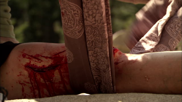 vidéos et rushes de an injured hiker wraps a scarf around a deep gash in her knee. - blessure physique