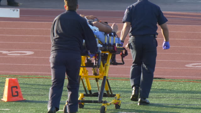 vídeos de stock, filmes e b-roll de an injured player taken in a stretcher with an injury while playing american football. - slow motion - dano físico
