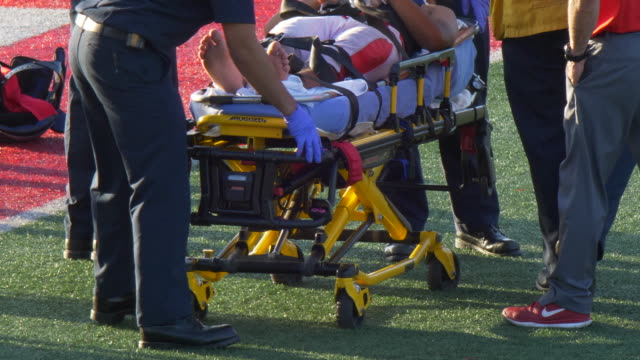an injured player taken in a stretcher with an injury while playing american football. - brain damage stock videos & royalty-free footage