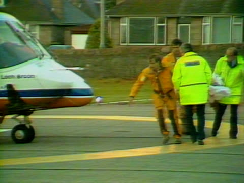 an injured survivor from the piper alpha disaster is transferred from an air ambulance in aberdeen to a waiting ambulance. 07 july 1988. - alpha cell stock videos & royalty-free footage