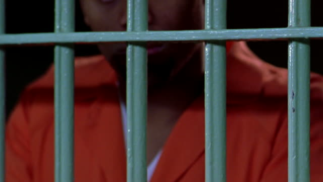 an inmate grabs the bars of his prison cell. - prisoner hands stock videos & royalty-free footage