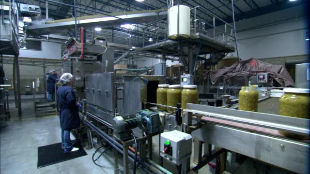 vídeos de stock e filmes b-roll de an inspector randomly checks a jar of relish on an assembly line. - bata cirúrgica
