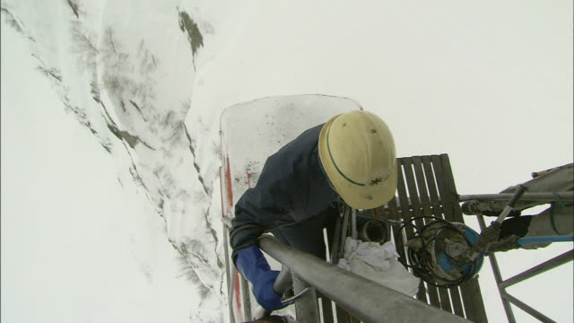 vídeos de stock e filmes b-roll de an inspector rides a cable car above a snowy slope on mount tateyama in japan. - cable