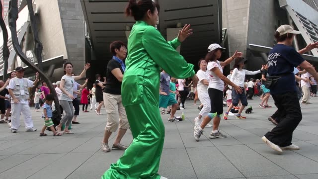 an instructor leads tai chi practice at the roppongi hills mori tower operated by mori building co in tokyo japan on saturday july 26 2014people... - roppongi hills stock videos and b-roll footage