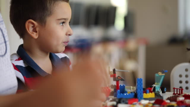 vidéos et rushes de un enfant d'âge préscolaire intéressé construisant quelque chose avec des blocs en plastique - construire