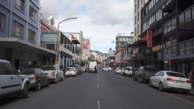 an interesting pov along a busy street in cape town towards building painted with the south african flag - cape town stock videos & royalty-free footage