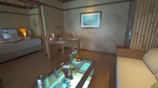an interior luxury resort hotel room living room in an overwater bungalow with a glass floor coffee table. - bora bora stock videos & royalty-free footage