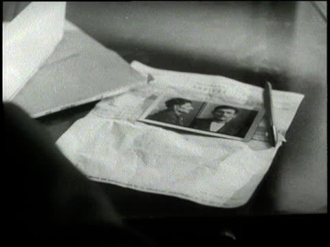 vídeos de stock e filmes b-roll de an interpol agent looks through photographs of criminals - fotografia de arquivo policial