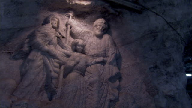 an intricate carving of figures is displayed on the wall of the italkali salt mine. available in hd. - carving craft product stock videos & royalty-free footage