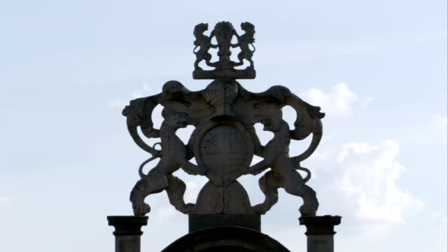 an intricate sculpture rises against a blue sky at burghley house. available in hd. - リンカンシャー点の映像素材/bロール