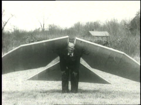 an inventor wearing the mechanical wings and tail of his ornithopter stands in a field. - skibrille stock-videos und b-roll-filmmaterial
