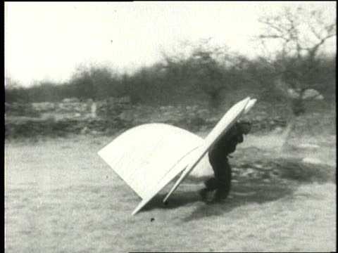 an inventor wearing the mechanical wings and tail of his ornithopter runs across a field in an attempt to fly - inventor stock videos & royalty-free footage