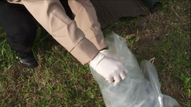 an investigator pulls camping supplies from a plastic bag. - 証拠点の映像素材/bロール