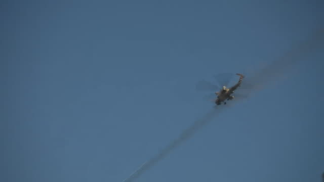 an iraqi army helicopter firing missiles at islamic state targets in western mosul - kampfhubschrauber stock-videos und b-roll-filmmaterial
