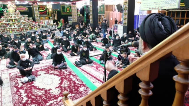an iraqi clergy man living in tehran delivers a sermon as he sits in the karbalaeiha hussainiyah during a religious ceremony to commemorate tasoua a... - ashura muharram stock videos & royalty-free footage