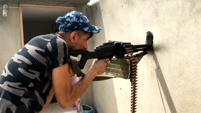 An Iraqi federal policeman fires a machine gun at a nearby Islamic State position in west Mosul Iraqi forces backed by US and British air support...