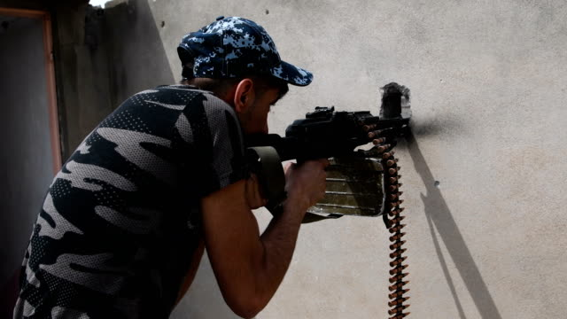 an iraqi federal policeman fires a machine gun at a nearby islamic state position in west mosul. iraqi forces backed by u.s and british air support... - machine gun stock videos & royalty-free footage